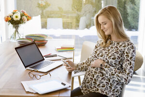 Smiling pregnant woman working from home - BMOF00001