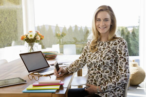 Portrait of smiling pregnant woman working from home - BMOF00004