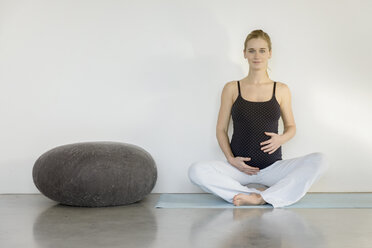 Portrait of smiling pregnant woman sitting on a yoga mat - BMOF00013