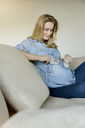 Smiling pregnant woman sitting on couch holding baby shoes - BMOF00019