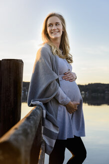 Smiling pregnant woman standing at lakeshore - BMOF00022