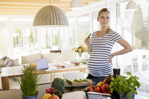 Smiling pregnant woman in kitchen at home eating cucumber - BMOF00025