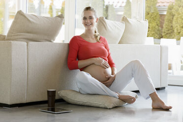 Portrait of smiling pregnant woman sitting on floor at home - BMOF00031