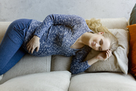 Pregnant woman sleeping on couch at home - BMOF00034