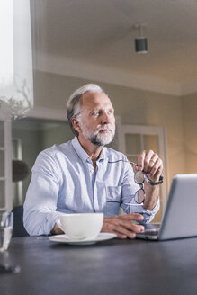 Portrait of pensive mature man sitting at table with laptop looking at distance - UUF12924