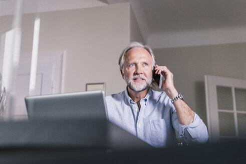 Portrait of mature man on the phone  at home - UUF12927