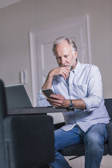 Mature man sitting at table with laptop looking at cell phone - UUF12933