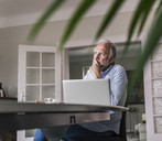 Pensive mature man sitting at table with laptop in his living room - UUF12936