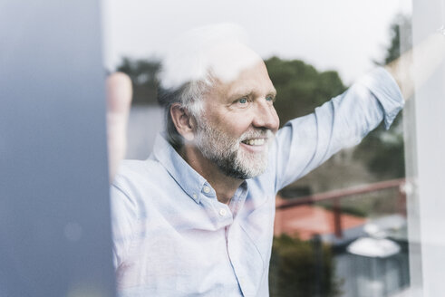 Portrait of happy mature man looking out of windowpane - UUF12942