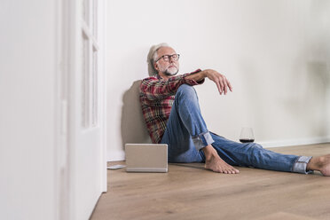 Barefoot man relaxing on the floor at home - UUF12951