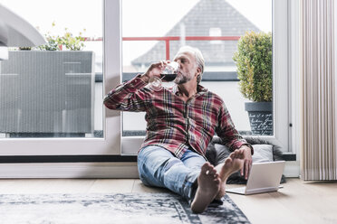 Barefoot man relaxing on the floor at home drinking glass of red wine - UUF12954