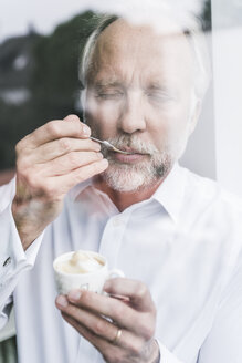 Portrait of mature man behind glass pane enjoying crema - UUF12960