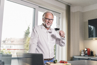 Portrait of smiling mature man standing in the kitchen with glass of red wine - UUF12963
