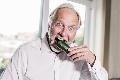 Portrait of mature man biting in courgette - UUF12966