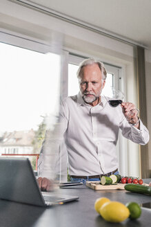 Portrait of mature man standing with glass of red wine in the kitchen looking at laptop - UUF12969