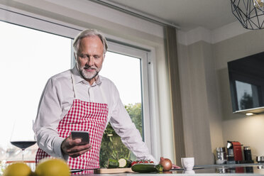 Portrait of mature man in the kitchen using cell phone - UUF12972