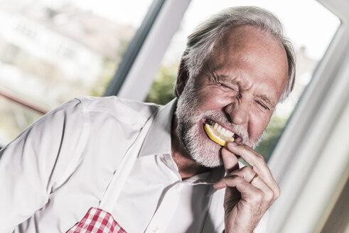 Portrait of man eating lemon slice - UUF12975