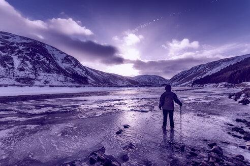 United Kingdom, Scotland, Highlands, female hiker standing at icy riverside - SMAF00952