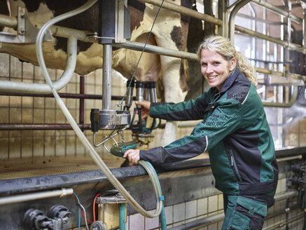 Portrait of smiling female farmer in stable milking a cow - CVF00249