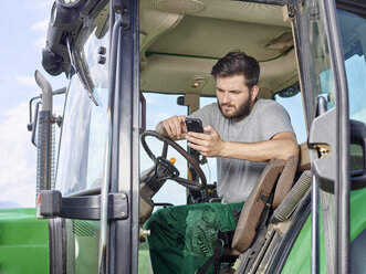 Farmer sitting on tractor using cell phone - CVF00258