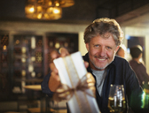 Portrait smiling senior man giving gift in bar - HOXF00003