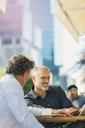 Businessmen using digital tablet at urban sidewalk cafe - HOXF00018