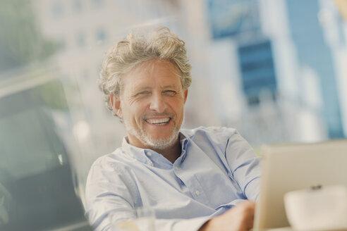 Portrait smiling businessman using digital tablet at sidewalk cafe - HOXF00024