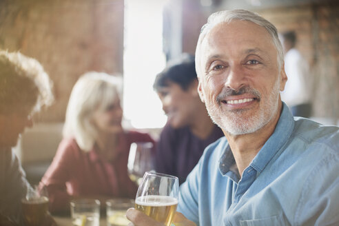 Portrait confident man drinking white wine with friends at restaurant table - HOXF00030