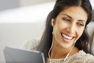 Close up smiling woman using digital tablet with headphones - HOXF00054