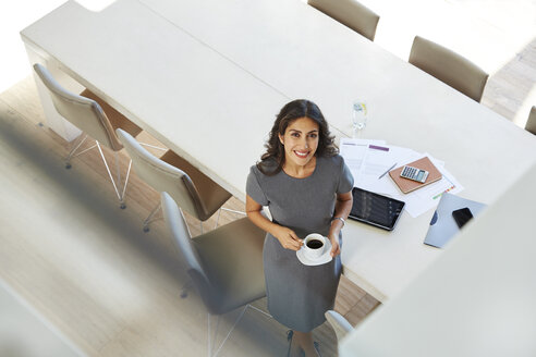 Portrait smiling businesswoman drinking coffee in conference room - HOXF00057