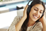Smiling woman listening to music with headphones and eyes closed - HOXF00063