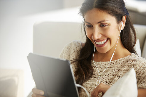 Smiling woman using digital tablet with headphones on sofa - HOXF00075