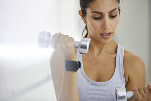 Focused woman doing biceps curls with dumbbells - HOXF00090