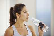 Woman drinking water post workout - HOXF00099