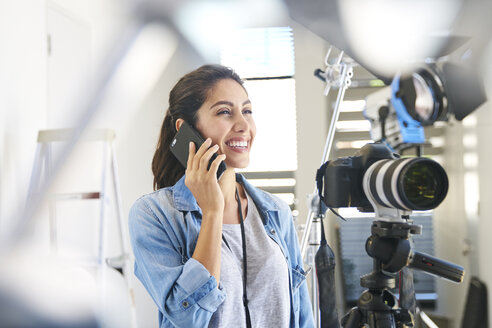 Smiling female photographer talking on cell phone behind camera in studio - HOXF00111