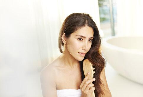 Serene brunette woman brushing hair in bathroom - HOXF00126