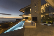 Illuminated luxury home showcase exterior and infinity lap pool with ocean view - HOXF00132