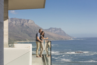Couple looking at sunny ocean view from luxury balcony - HOXF00135