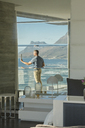 Reflection of man using digital tablet camera on luxury balcony with ocean view - HOXF00138