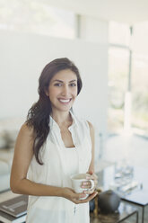 Portrait smiling brunette woman drinking coffee in living room - HOXF00144