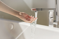 Woman touching water from modern bathtub faucet - HOXF00147