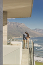 Couple looking at sunny ocean and mountain view from luxury balcony - HOXF00159