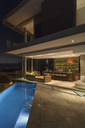 Illuminated luxury home showcase bar and patio with lap pool at night - HOXF00168