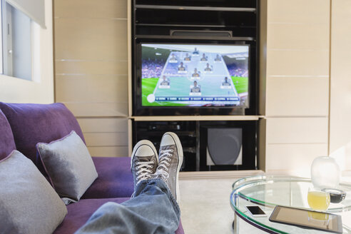 Personal perspective man with feet up watching soccer game on TV in living room - HOXF00180