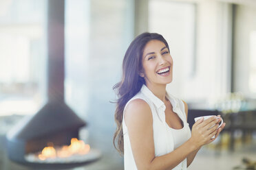Portrait smiling woman drinking coffee near fireplace - HOXF00183