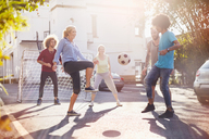 Friends playing soccer in sunny summer street - CAIF04203