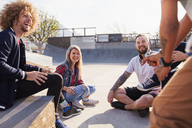 Friends talking and hanging out at sunny skate park - CAIF04209