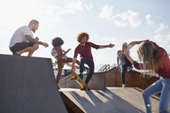 Woman photographing male friends skateboarding on ramp at sunny skate park - CAIF04215