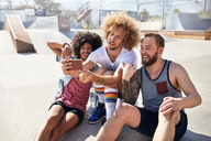 Male friends with camera phone taking selfie at sunny skate park - CAIF04227