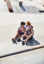 Overhead view male friends taking selfie with camera phone at sunny skate park - CAIF04236